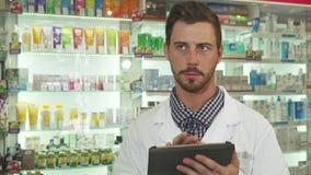 El droguero examina inventario de las drogas con la tableta digital metrajes