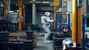 El droid biónico camina en un cuarto y tipos de la fábrica en una tableta almacen de video