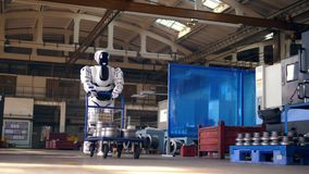 El droid masivo está transportando una carretilla a través de la fábrica almacen de metraje de vídeo