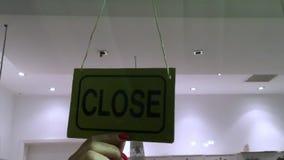 El dueño de tienda que da vuelta abierto firma adentro la entrada de la tienda almacen de metraje de vídeo