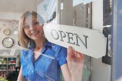 El dueño de tienda que da vuelta abierto firma adentro la entrada de la tienda Foto de archivo libre de regalías
