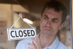 El dueño de tienda que da vuelta cerrado firma adentro la entrada de la tienda Foto de archivo