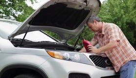 El dueño de vehículo comprueba el aceite Imagen de archivo libre de regalías