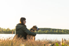 El dueño del perro y su animal doméstico se sientan en el riverbank en la puesta del sol fotos de archivo