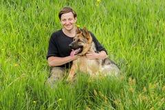 El dueño feliz abraza su perro Entrenamiento del pastor alemán Imagen de archivo
