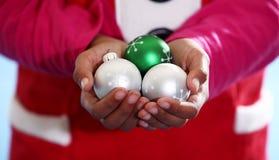 El duende de la Navidad sostiene los ornamentos Imagen de archivo libre de regalías