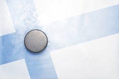 El duende malicioso de hockey viejo está en el hielo con la bandera finlandesa Imagenes de archivo