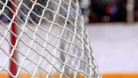 El duende malicioso de hockey vuela en la red en tableros de un hockey con una raya amarilla en la cámara lenta almacen de metraje de vídeo