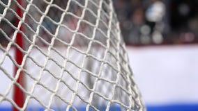 El duende malicioso de hockey vuela en la red en tableros de un hockey con una raya azul en la cámara lenta
