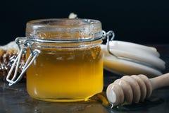 El dulce condimentó la miel en el peine con una cuchara en la cacerola En bla Imagenes de archivo