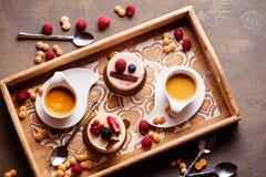 El dulce se apelmaza con las bayas en el primer de la tabla con la taza de café express imagen de archivo libre de regalías