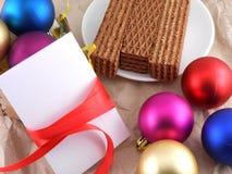 El dulce se enrolla con las bolas de la Navidad y la tarjeta en blanco de la invitación Imagen de archivo libre de regalías