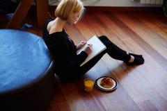El dulce y el artista muy apacible que se sientan en el piso y dibujan un lápiz Fotografía de archivo libre de regalías