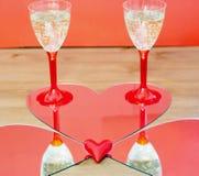 El duplicar de dos vidrios del champán y de poco corazón Imágenes de archivo libres de regalías