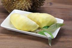 El Durian y el Durian hojean en el plato blanco, fondo de madera Fotografía de archivo