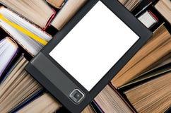 El eBook con una pantalla blanca miente en los libros multicolores abiertos que mienten en un fondo oscuro, primer foto de archivo