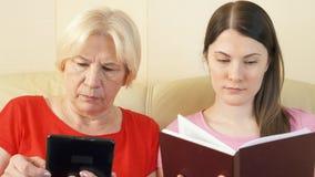 El eBook de la lectura de la madre y de la hija y la impresión física reservan Concepto de papel contra la lectura digital almacen de video