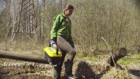El ecologista en la tala del bosque camina en corriente de la primavera almacen de video