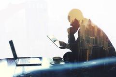 El economista pensativo está leyendo noticias en red vía la tableta digital Imagen de archivo
