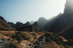 el edificio abandonado en el medio de uno de los valles en la puesta del sol con la hierba amarilla, los altos acantilados y dios imágenes de archivo libres de regalías