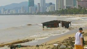 El edificio arruinado rasgado de orilla flota en el mar después de tifón