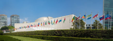 El edificio de la Asamblea General de la O.N.U Naciones Unidas con las banderas del mundo vuela imagenes de archivo