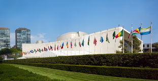 El edificio de la Asamblea General de la O.N.U Naciones Unidas con las banderas del mundo vuela Fotografía de archivo