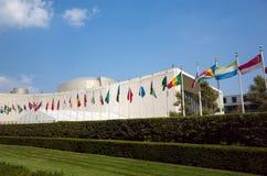 El edificio de la Asamblea General de la O.N.U Naciones Unidas con las banderas del mundo vuela Fotografía de archivo libre de regalías