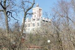 El edificio de ladrillo de varios pisos entre árboles Fotos de archivo libres de regalías