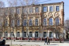 El edificio de ladrillo de varios pisos entre árboles Fotos de archivo
