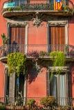 El edificio en Barcelona hizo de los ladrillos rojos, opinión al aire libre sobre balcón con las flores Fotos de archivo libres de regalías