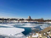 El edificio hermoso en fondo, nieve e hielo cubrió el agua en primero plano foto de archivo