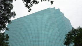 El edificio moderno con las ventanas vidriosas a través de la corona de árboles, enfoca adentro almacen de metraje de vídeo