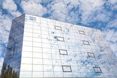 El edificio moderno hecho del vidrio es soporte en fondo de un cielo nublado azul Visión izquierda Imágenes de archivo libres de regalías
