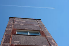 El edificio y el rastro de aeroplano en cielo Imagen de archivo