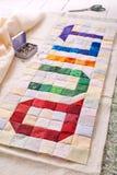 El edredón de la palabra cosido de pedazos coloridos del cuadrado y del triángulo de tela foto de archivo libre de regalías