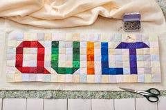 El edredón de la palabra cosido de pedazos coloridos del cuadrado y del triángulo de tela imagenes de archivo