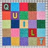 El edredón de la palabra integrado por las letras de madera coloreadas presentadas en pedazos coloridos de telas dispuestas en la foto de archivo