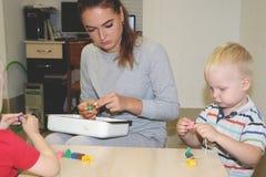 El educador trata del niño en la guardería Creatividad y desarrollo del niño fotografía de archivo libre de regalías