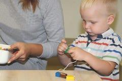 El educador trata del niño en la guardería Creatividad y desarrollo del niño foto de archivo libre de regalías