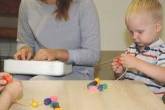 El educador trata del niño en la guardería Creatividad y desarrollo del niño fotos de archivo