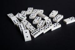 El efecto de dominó caido de los dominós pierde el fondo del negro del concepto del fall Foto de archivo libre de regalías