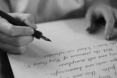 El efecto retro se descoloró y entonó imagen de una muchacha que escribía una nota con una letra manuscrita de la antigüedad de l Fotos de archivo libres de regalías
