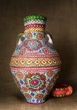 El egipcio colorido handcrafted el tarro de cerámica adornado artístico en fondo de la harpillera Foto de archivo