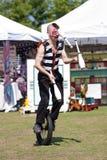 El ejecutante de circo hace juegos malabares mientras que monta el Unicycle Fotos de archivo libres de regalías
