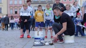El ejecutante de la calle muestra apagado sus habilidades de la percusión en un cubo simple y platos