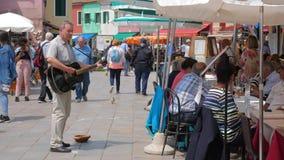 El ejecutante de la calle recoge el dinero tocando la guitarra en el cuadrado con la gente