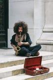 El ejecutante juega el saxofón en Wall Street, NY Fotografía de archivo libre de regalías