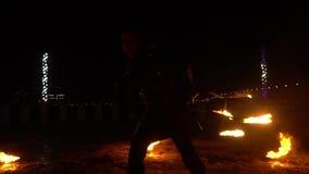 El ejecutante masculino hace girar una silla ardiente en una demostración del fuego en la calle almacen de metraje de vídeo