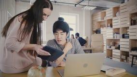 El ejecutivo de sexo femenino hermoso ayuda al colega asiático en su tabla Hombres de negocios multiétnicos del trabajo en la ofi metrajes